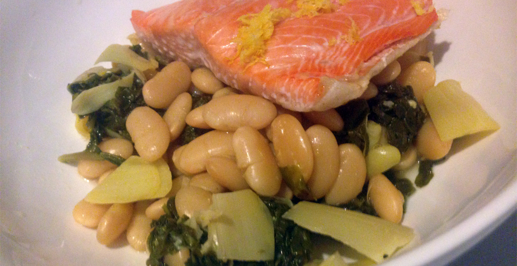 White beans braised with kale and artichokes, topped with slow roasted salmon.