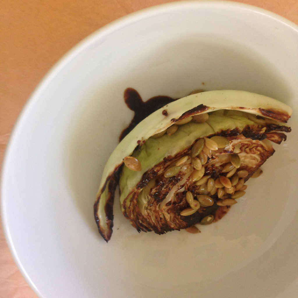 Grilled cabbage with pomegranate molasses and toasted pumpkin seeds.