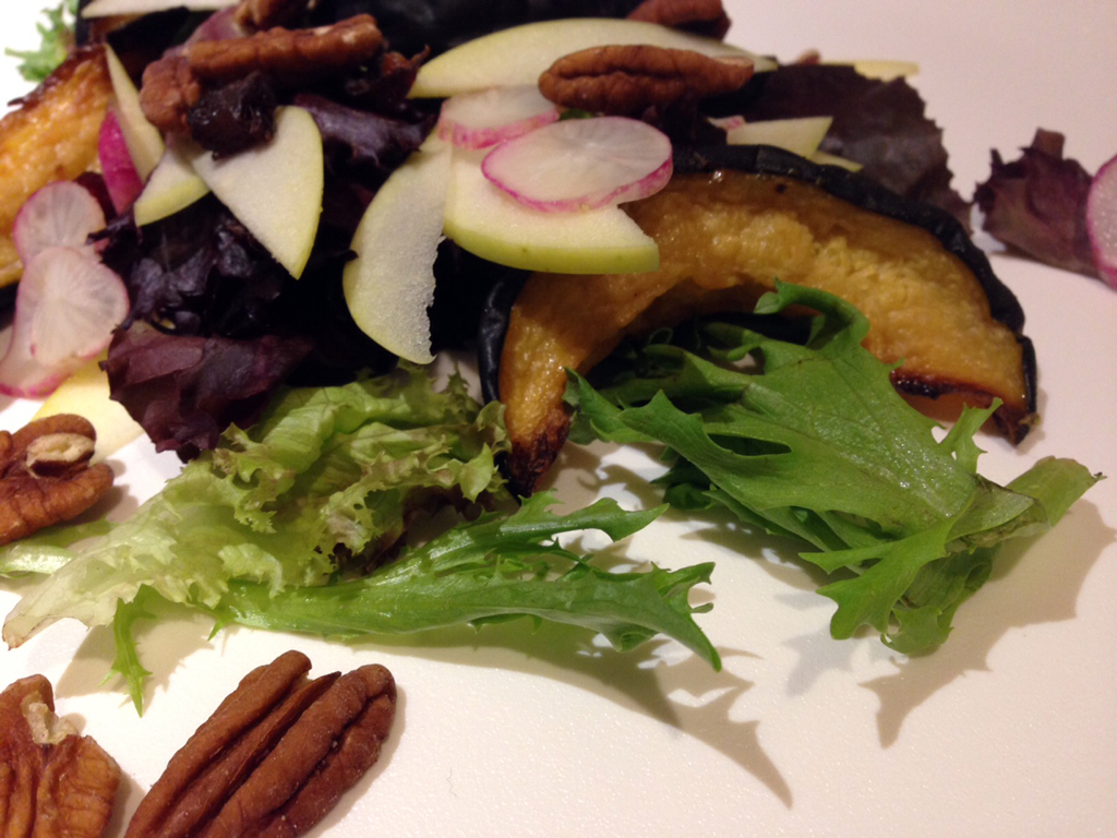 Salad of roasted acorn squash, shaved apple and radish, greens, and toasted pecans.