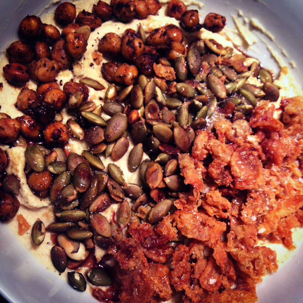 Hummus topped with crispy chickpeas, toasted pumpkin seeds, and fried chicken skin.