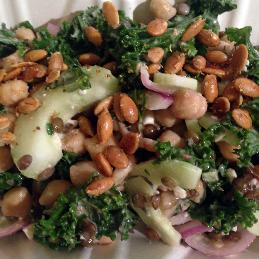 Chickpea and lentil salad with kale, cucumbers, feta, and toasted pepitas.