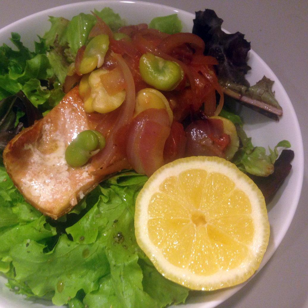 Seared salmon with braised tomatoes and fava beans over leaf lettuce.