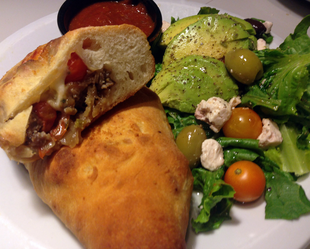 Sausage calzone, with caramelized onions and fennel. Tossed salad with lettuce, avocado, tomato, olive, and feta.